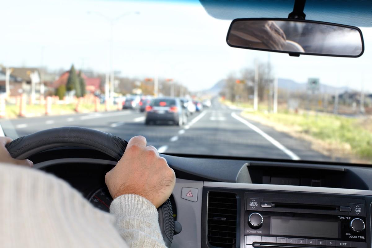 kierowca w aucie na drodze